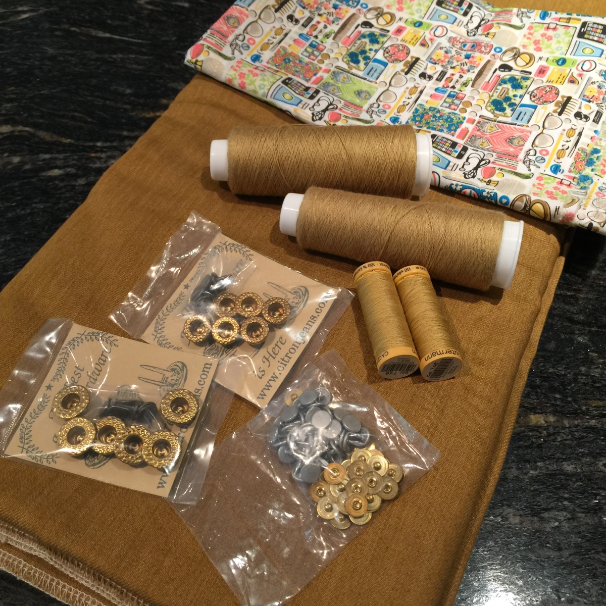photo of brass fittings and top stitching thread to be used next to pocket fabric