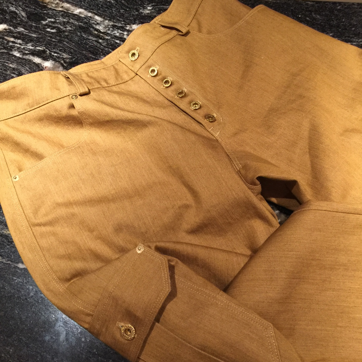 flat lay close up of tan cargo pants highlighting brass hardware and top stitching.