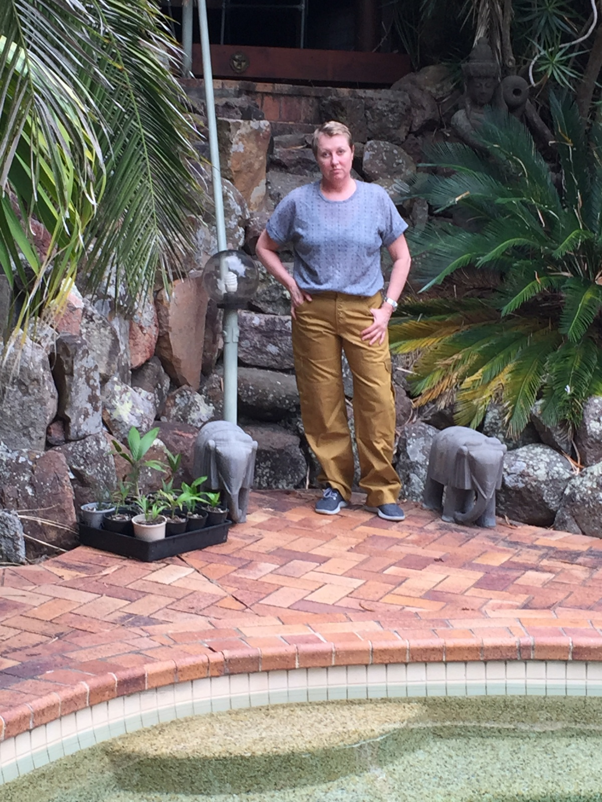 Michelle standing buy a lovely in-ground pool in tan cargo pants made from Jutland pattern