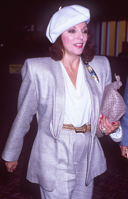Image of Joan Collins in the 1980's wearing a silver power suit with padded shoulders and a white beret.